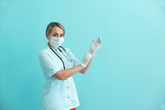 Vrouwenarts of verpleegster die een masker, een toga en een stethoscoop dragen die op chirurgische handschoenen zetten