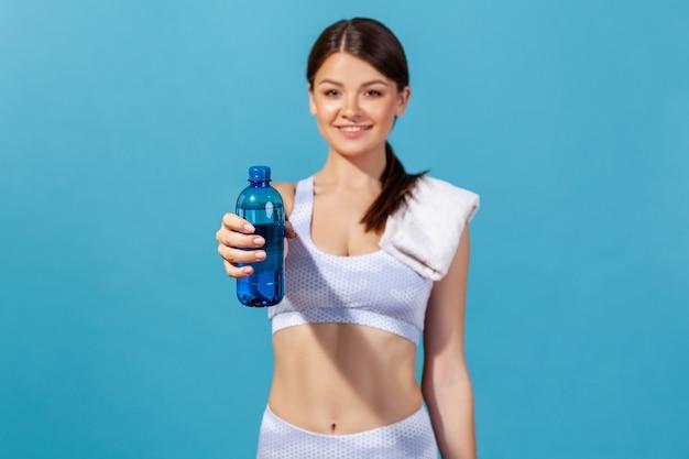 Vrouwenatleet die blauwe fles met mineraalwater vasthoudt en laat zien, waardoor elektrolyten worden hersteld