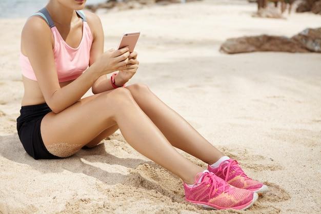 Vrouwenatleet die haar vrienden online overseinen met behulp van slimme telefoon terwijl het ontspannen op strand na het runnen van training. jonge sportvrouw in roze loopschoenen die sms op elektronisch apparaat tijdens onderbreking texting