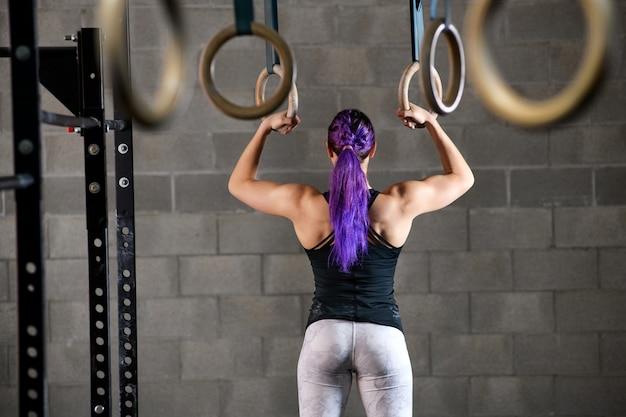 Vrouwenatleet die op de ringen voorbereidingen treffen uit te werken