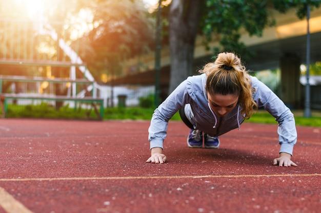 Vrouwenatleet die opdrukoefening op de renbaan doen