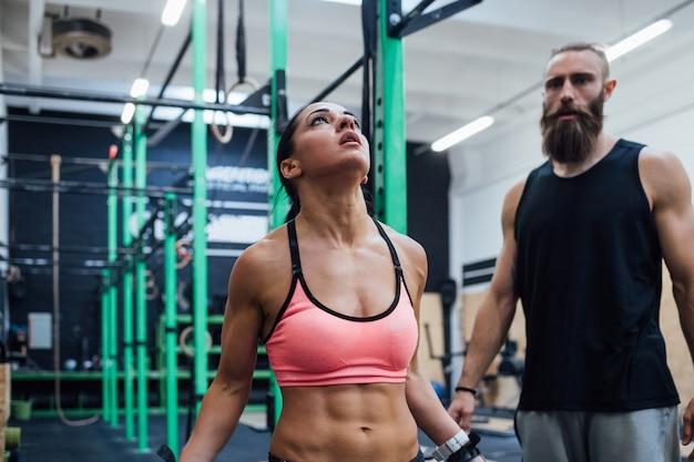 Vrouwenatleet die voor het bereiken van gymnastiek- ring met persoonlijke trainer voorbereidingen treffen