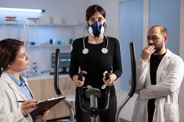 Vrouwenatleet met masker die fitnessoefeningen doet in het wetenschapssportlaboratorium met elektroden eraan bevestigd terwijl wetenschapper met klembord toezicht houdt op het hele proces. arts met behulp van kladblok controle ecg-gegevens.