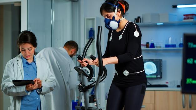 Vrouwenatleet met masker die op crosstrainer loopt in een sportwetenschappelijk laboratorium dat prestaties en zuurstofverbruik meet tijdens de vo2max-test. medisch onderzoeker kijkt naar ecg-scan monitoring hartslag