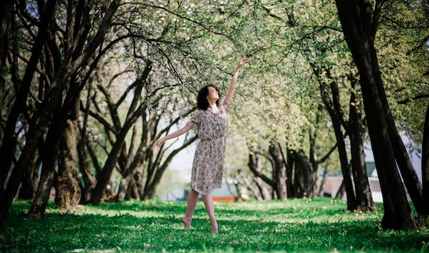 Vrouwenballerina in bloeiende tuin. roze. ballet. portret van dansend meisje buiten.