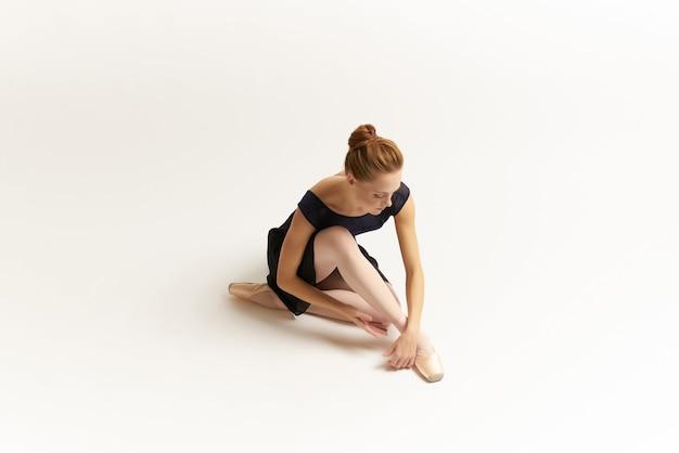 Vrouwenballerina in zwart kostuum die danssilhouet uitvoeren