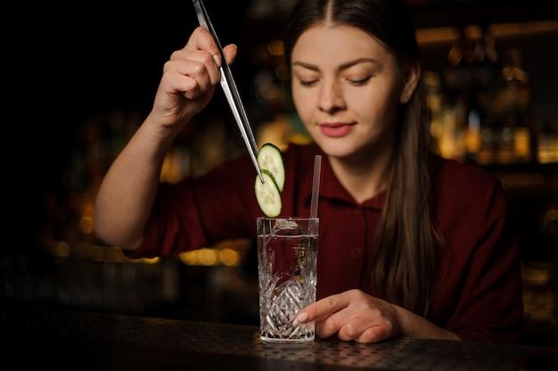 Vrouwenbarman die een verse cocktail met jenever en komkommer maken