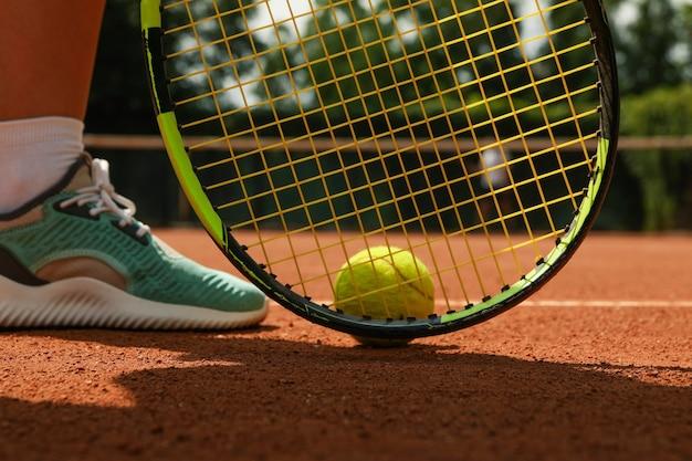 Vrouwenbeen, racket en tennisbal op gravel