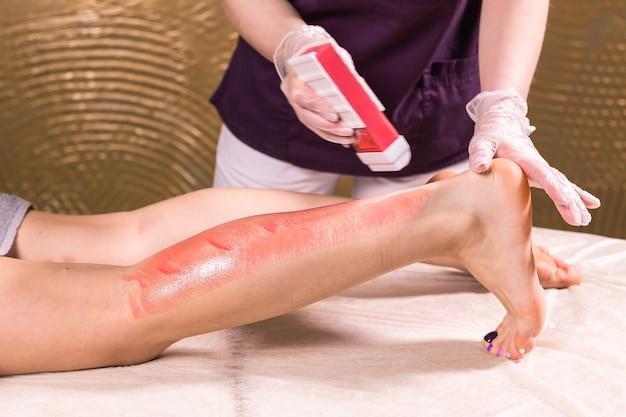 Vrouwenbeen waxen. procedure voor het epileren van de salonwas schoonheidsspecialiste waxen vrouwelijk lichaam voor ontharing door