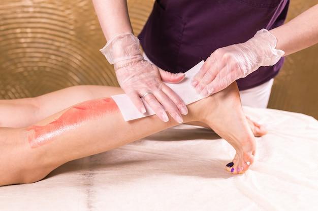Vrouwenbeen waxen. procedure voor het epileren van de salonwas schoonheidsspecialiste. waxen vrouwelijk lichaam voor ontharing door