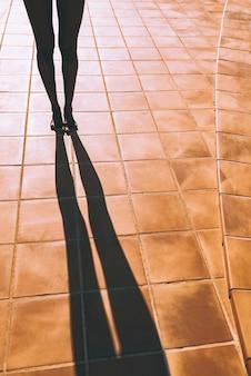 Vrouwenbenen die een schaduw op de vloer maken
