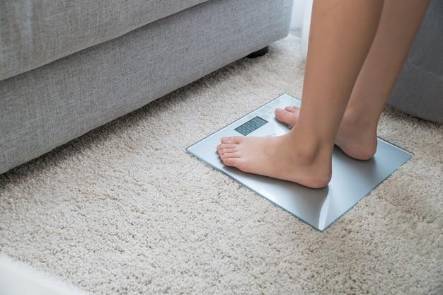 Vrouwenbenen die zich op schalen bevinden, bevindt de vrouw die op weegt thuis zich weegt.