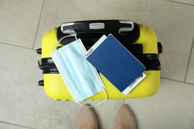 Vrouwenbenen en koffer met masker en paspoort met kaartje en covid - 19 merkteken
