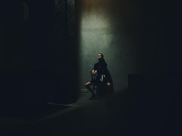 Vrouwenbenen gespreid zit op een stoel in een donkere kamer en vallend licht interieurmodel