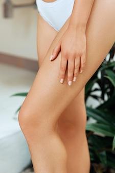 Vrouwenbenen in badkamers. schoonheid en lichaamsverzorging.