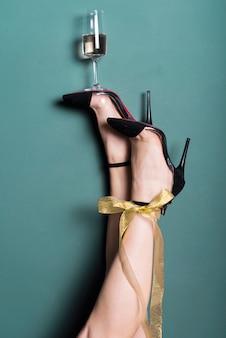 Vrouwenbenen in hielen die glas champagne houden