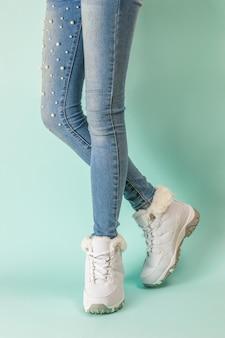 Vrouwenbenen in witte sneakers en strakke spijkerbroek. wintersportstijl.