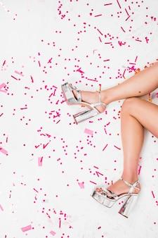Vrouwenbenen in zilveren schoenen bij partij