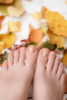 Vrouwenbenen met herfst nageldesign op houten oppervlak met gevallen bladeren.