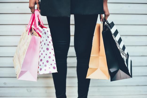 Vrouwenbenen met kleurrijke het winkelen zakken