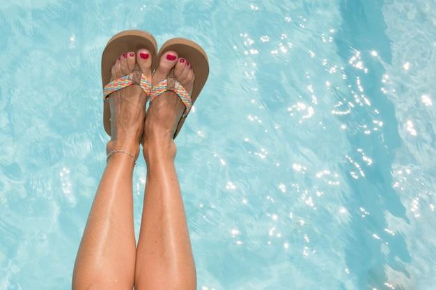 Vrouwenbenen met rode spijkerans schoenen in zwembad