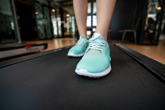 Vrouwenbenen met sportschoenen die op loopband in geschiktheidsgymnastiek lopen.