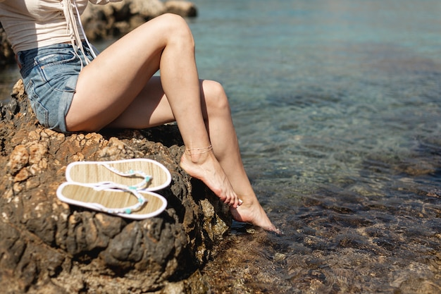 Vrouwenbenen met waterachtergrond