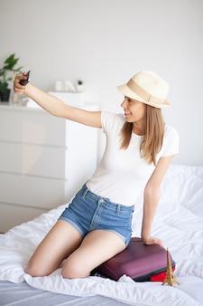 Vrouwenbenen omhoog op de bagage, jonge vrouw die thuis in bed leggen. de witte slaapkamer.