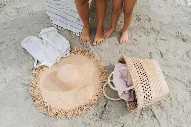 Vrouwenbenen, strohoed, zak leislinger van wit zand op een overzees strand.