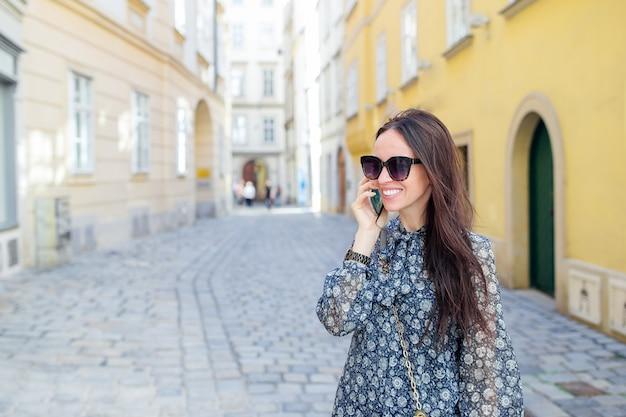 Vrouwenbespreking door haar smartphone in stad. jonge aantrekkelijke toerist in openlucht in italiaanse stad