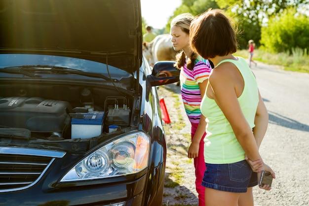 Vrouwenbestuurder met kind op landweg, dichtbij gebroken auto