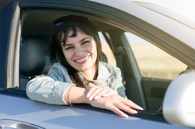 Vrouwenbestuurder met mooie glimlach en witte tanden.,