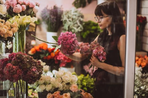 Vrouwenbloemist bij haar eigen bloemenwinkel die bloemen behandelen