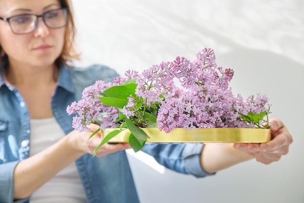 Vrouwenbloemist met lila bloemendecoratie
