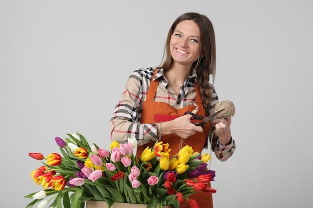 Vrouwenbloemist op een grijze achtergrond met tulpen