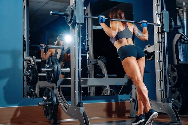 Vrouwenbodybuilder die hurkzit in een gymnastiek doen