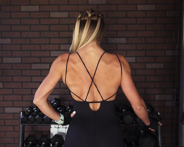 Vrouwenbodybuilder die rugspieren in gymnastiek tonen