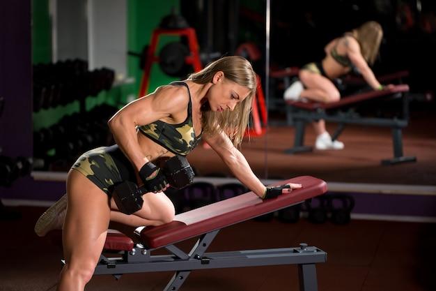 Vrouwenbodybuilder in gymnastiek opheffende domoren op bank