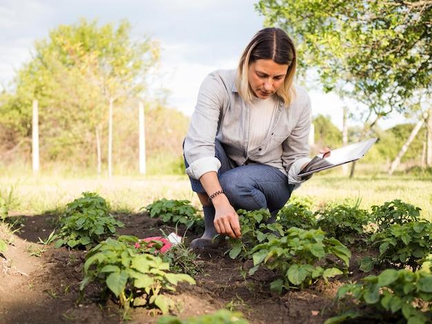 Vrouwenboer die haar tuin controleren