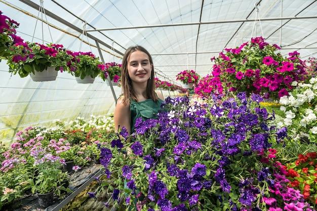 Vrouwenboer die in een tuincentrum werkt en voor haar verschillende bloemen zorgt. lente