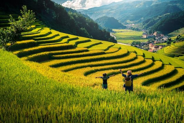 Vrouwenboer en dochter die wapen op padievelden opheffen terrasvormig bij zonsondergang in vietnam.