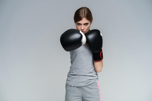 Vrouwenbokser in handschoenen die op grijs opleiden