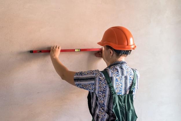 Vrouwenbouwer die muur met waterspiegel meet