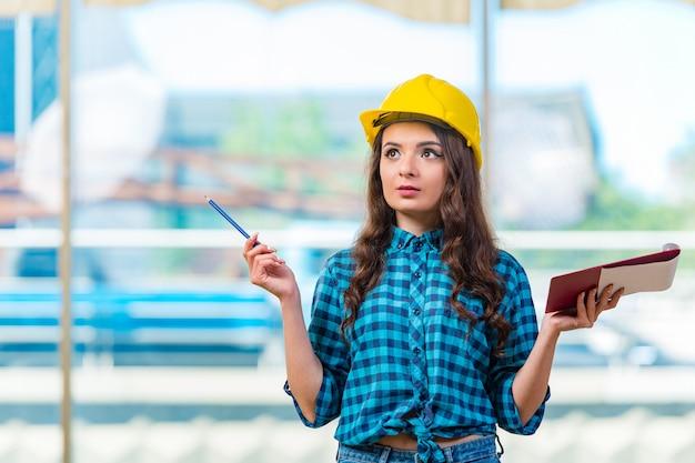 Vrouwenbouwer die nota's nemen bij bouwwerf