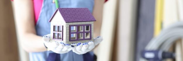 Vrouwenbouwer die stuk speelgoed houten huis in handenclose-up houdt