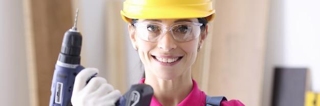 Vrouwenbouwer in beschermende helm die boor in haar handen houdt