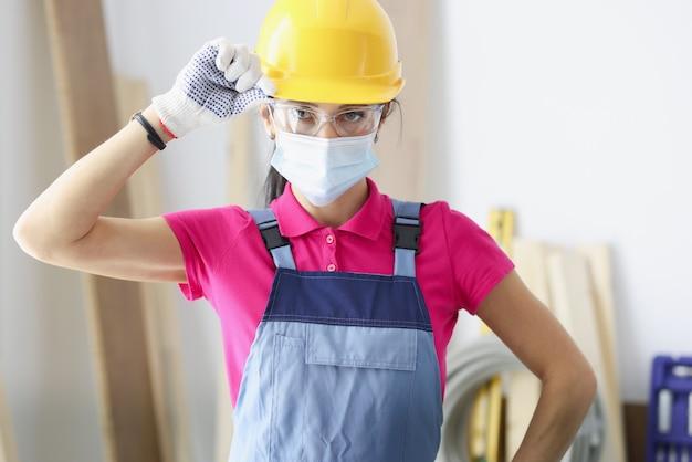 Vrouwenbouwer in gele bouwvakker en beschermend masker