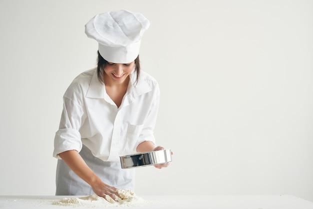 Vrouwenchef-kok die deeg kneedt die met meelprofessional werkt