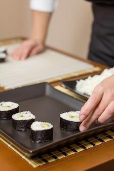 Vrouwenchef-kok die japanse sushibroodjes op een dienblad plaatsen