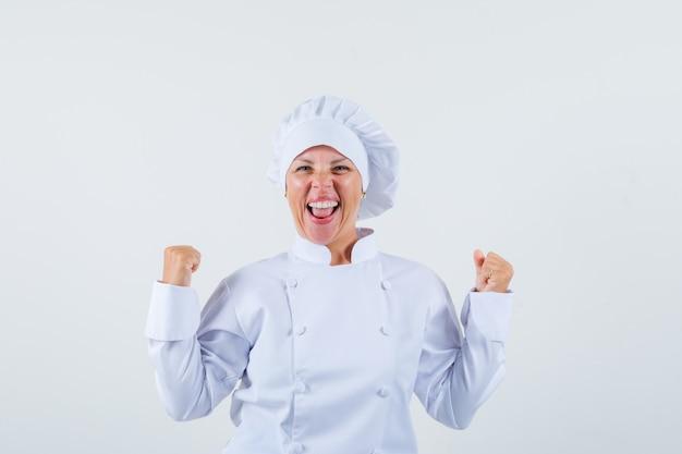 Vrouwenchef-kok die winnaargebaar in wit uniform toont en gelukkig kijkt.
